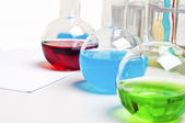Lab flasks with colored liquids, lab workplace — Stock Photo