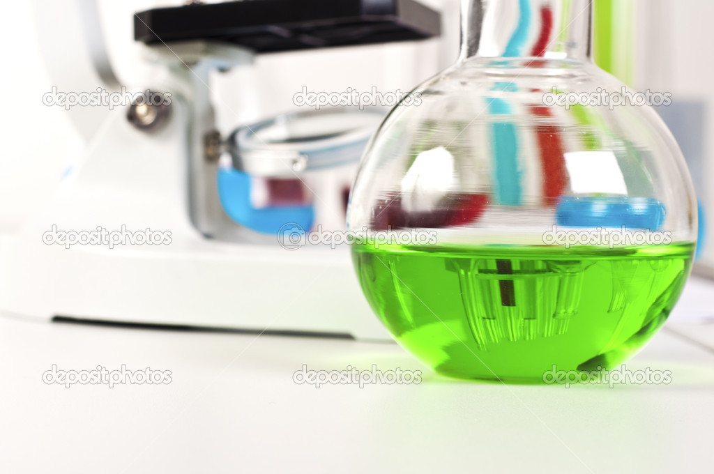 Lab bottle with green liquid, in the background microscope and other items — Stock Photo #6802237