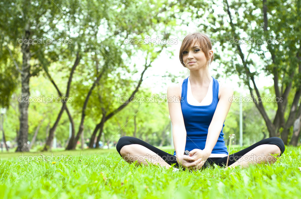 Young woman is engaged in yoga, in summer forest on a green grass — Stock Photo #7072429