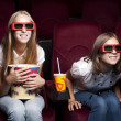 Two beautiful girls watching a movie at the cinema — Stock Photo #7641075