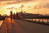 Boy on bike sunset — Stock Photo