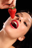 Red lips young woman eating fresh strawberry fruit — Stock Photo