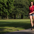 Sexy young woman roller skating in park sunshine — Stock Photo