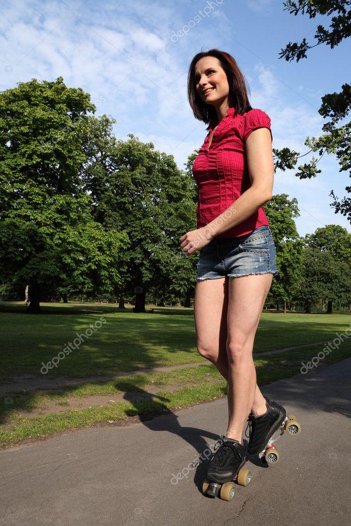 summer fun sexy long legged woman roller skating stock
