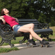 Beautiful roller skater woman sun tans in the park — Stock fotografie