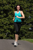 Happy fit woman jogging exercise in park sun — Stock Photo