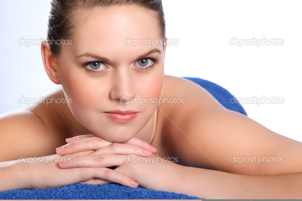 Beautiful young woman, lying naked on her front in health spa for beauty ...