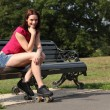 Cheerful skater girl sitting in sun on park bench — Stock Photo