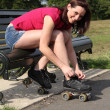 Beautiful girl ties roller skates on park bench — Stockfoto