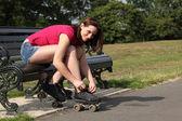 Fun time in sun beautiful girl putting on skates — Stock Photo