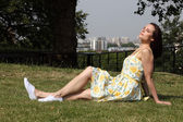 Beautiful woman in yellow dress enjoys summer sun — Stock Photo