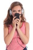 Cute teenager girl listens to music on headphones — Stock Photo