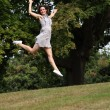 High flying jump for joy beautiful girl in park — Stock Photo