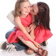 Kiss on cheek a mothers love to young daughter — Stock Photo