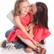 Stock Photo: Kiss on cheek a mothers love to young daughter