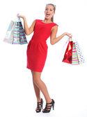 Mulher feliz sexy vestido vermelho presente sacos de compra — Fotografia Stock