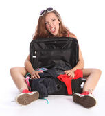 Teenager girl crazy fun packing for holiday travel — Stock Photo