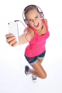 Happy sexy teenage girl has music fun with phone stock image