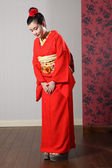 Oriental model in red Japanese kimono bowing — Stock Photo
