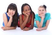 Black white and asian girl friends lying on floor — Stock Photo