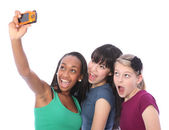 Three teenage girl friends fun with digital camera — Stock Photo