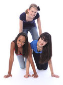 Mixed race teenage girl friends in fun pyramid — Stock Photo