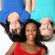 Three mixed race teenage girl friends on floor - Stockfoto