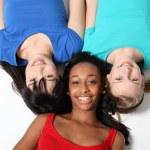 tre blandras tonårig flicka vänner på golvet — Stockfoto