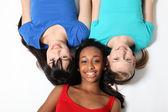 Three mixed race teenage girl friends on floor — Stock Photo