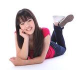 Oriental teenager high school girl lying on floor — Stock Photo