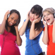Teenage girls singing to music on mobile phones — Stock Photo