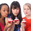 Teenage girl friends blowing out birthday candles — Stock Photo #7256393