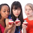 Teenage girl friends blowing out birthday candles — Stock Photo
