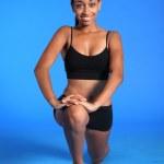 Kneeling hip flexor stretch by fit black woman — Stock Photo #7426129