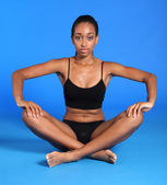 Athletic african fitness woman sits cross legged — Stock Photo