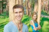 Smiling young boy and a girl at the background — Stock Photo
