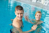 Splashing couple at the pool — Stock Photo
