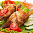 Two whole quail with cucumber, tomatoes and onion - Stock Photo