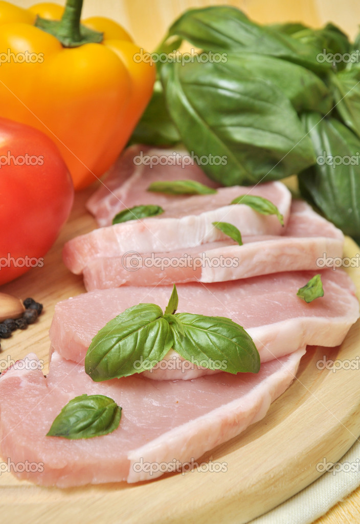 Raw meat on a cutting board with basil and vegetables — Stock Photo #6928299