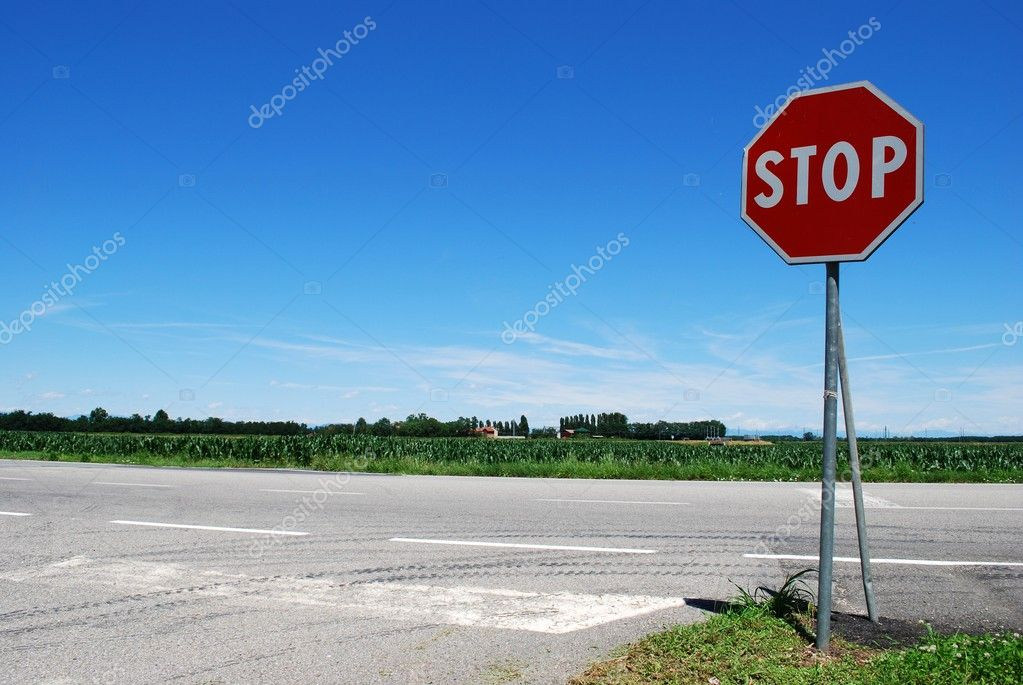Stop sign in a country road on blue sky — Stok fotoğraf #6911330