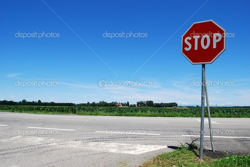 Stop sign in a country road on blue sky — Stock fotografie #6911330