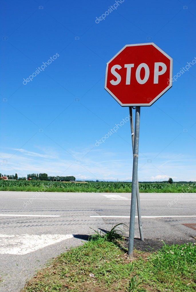 Stop sign in a country road on blue sky — Stock Photo #6911360