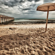 Umbrella and Pier at the Beach — Stock Photo