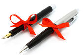 Fountain pen and ball pen with red bow — Stock Photo