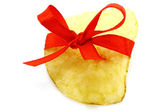 Single potato chip with red bow — Stock Photo