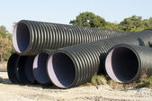 Pipes and piles of sand in the background — Stock Photo