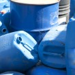 Old colored oil barrels and blue canisters - Stock Photo