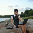 Office by the sea: the girl on the rocks with a laptop and a desktop phone — Stock Photo #6932927