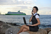 Office by the sea: the girl on the rocks with a laptop and a desktop phone — Foto Stock