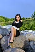 Girl sitting on rocks and smiling — Stok fotoğraf
